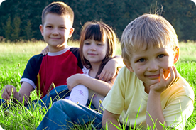 Children sitting in the grass.
